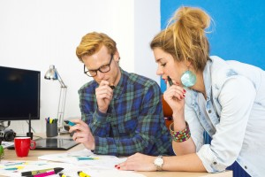 Two colleagues working together on an innovative product design in a creative studio behind a desk, littered with markers, sketches, drawings and